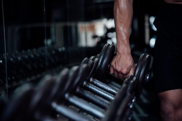 Молодой человек в спортивной одежде упражнения в тренажерном зале Бесплатные Фотографии