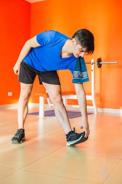 Молодой человек в спортивной растяжке перед тренировкой в тренажерном зале - портрет фитнес-центра, делающего упражнения на растяжку в тренажерном зале. Premium Фотографии