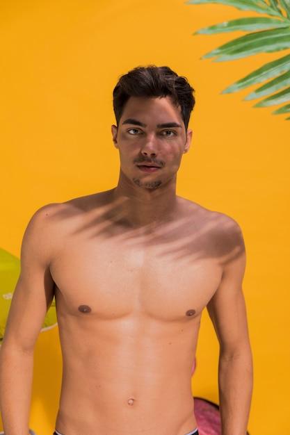 Молодой человек в купальных костюмах на пляже Бесплатные Фотографии