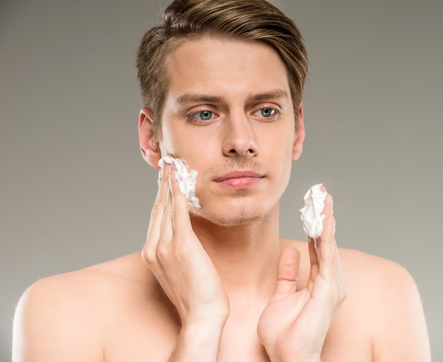 Young man is applying shaving cream to his face. Premium Photo