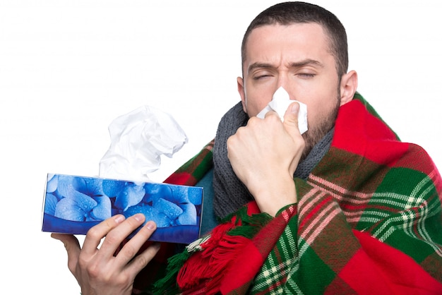 Young man is blowing his nose in a handkerchief. Premium Photo