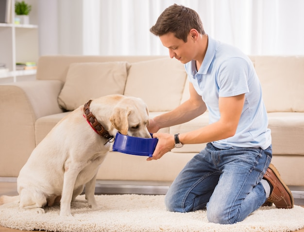 Young man is feeding his dog sitting on the floor. Premium Photo