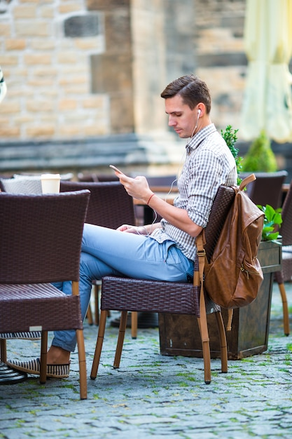 Young man is holding cellphone outdoors on the street. guy using mobile smartphone. Premium Photo