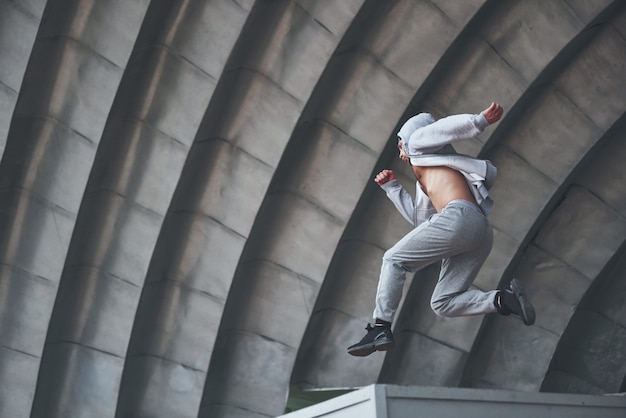 Un giovane sta saltando. parkour nello spazio urbano, attività sportiva. Foto Gratuite