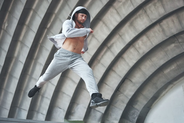 A young man is jumping. parkour in urban space, sporting activity. Free Photo