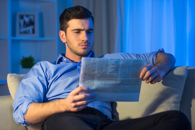 Young man is reading a newspaper at home. Premium Photo