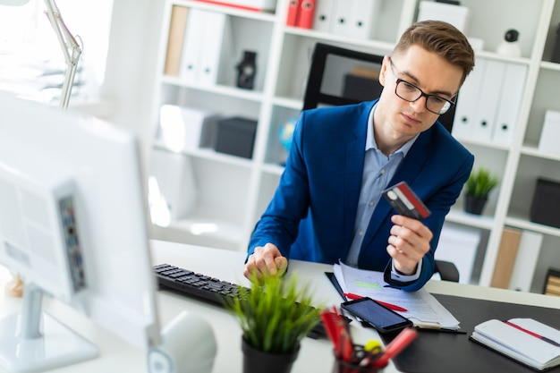 A young man is sitting at a table in the office, holding a bank card in his hand and typing on a computer. Premium Photo