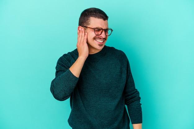 手で耳を覆う青い壁に孤立した若い男 Premium写真