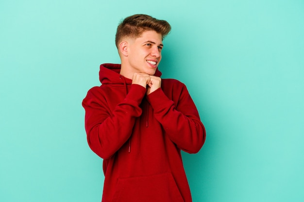 파란색 벽에 고립 된 젊은 남자가 턱 밑에 손을 유지하고 행복하게 옆으로 찾고 있습니다. 프리미엄 사진