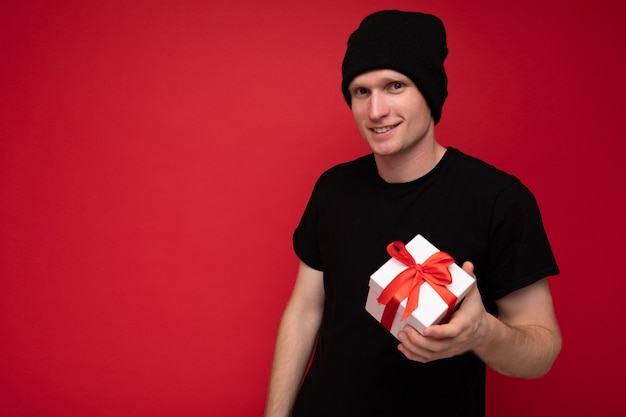 Young man isolated over red background wall wearing black hat and black t-shirt holding white gift box with red ribbon and looking at camera. copy space, mockup Premium Photo