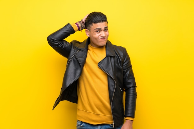 Young man over isolated yellow background having doubts while scratching head Premium Photo