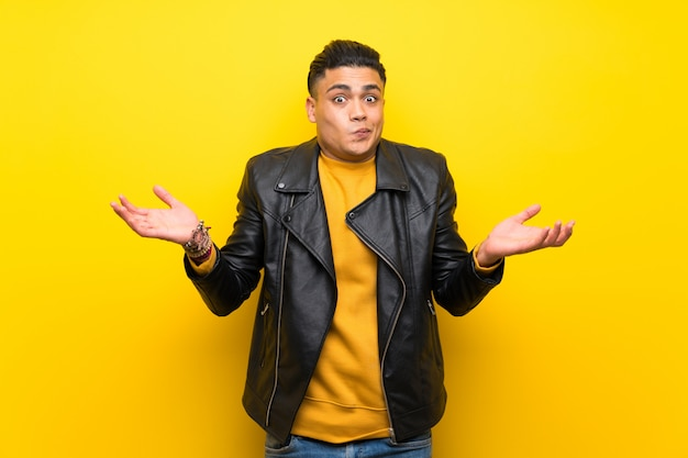 Young man over isolated yellow wall having doubts while raising hands Premium Photo