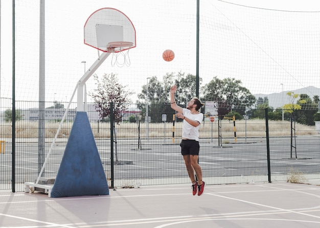 Young man jumping and throwing basketball in hoop Free Photo