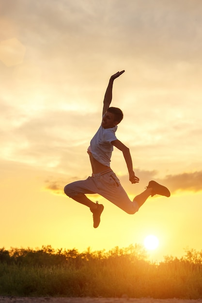 Young man jumping up against the sunset sky Premium Photo