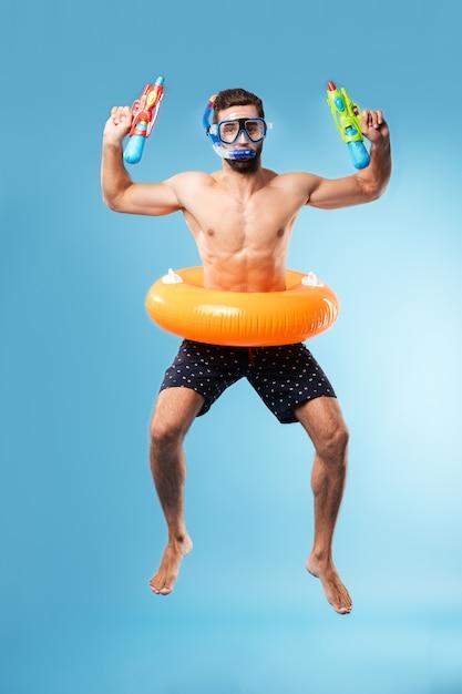 Giovane che salta indossando il cerchio e gli occhiali di nuoto Foto Gratuite
