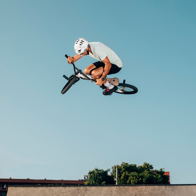 Young man jumping with bmx bike in a skatepark Free Photo