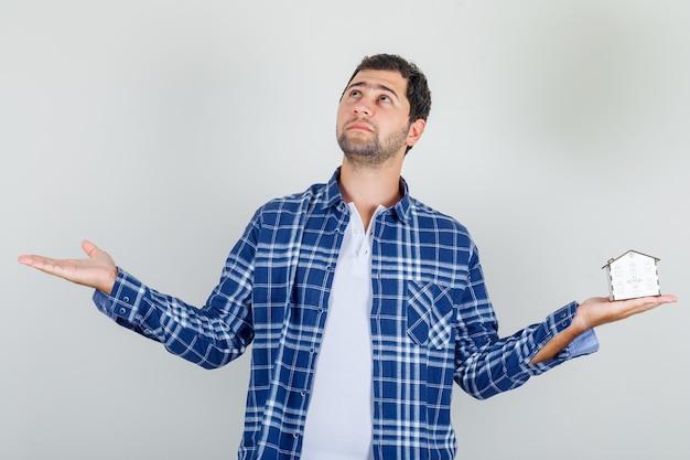 Молодой человек держит открытые руки с моделью дома в рубашке и выглядит обнадеживающим. Бесплатные Фотографии