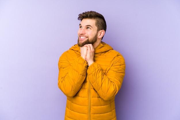Молодой человек держит руки под подбородком, радостно смотрит в сторону. Premium Фотографии