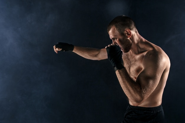 The young man kickboxing on black copyspace Free Photo