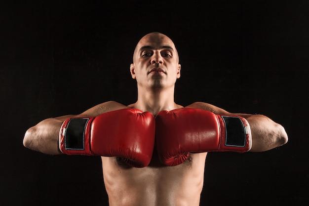 Young man kickboxing on black Free Photo