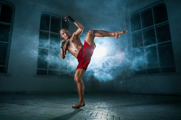 The young man kickboxing in blue smoke Free Photo