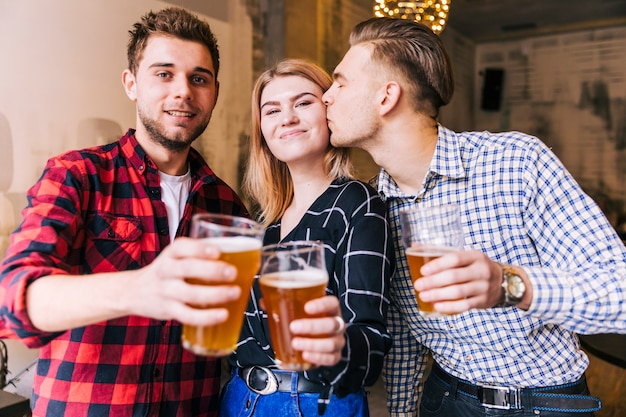 Young man kissing her girlfriend while toasting the beer glasses with friend Free Photo