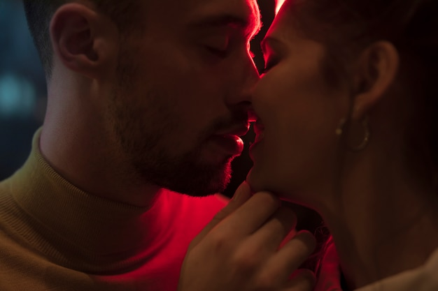 Young man kissing smiling woman near red lights Free Photo
