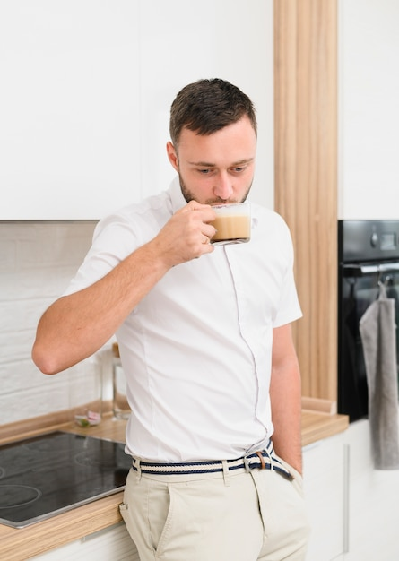Young man in the kitchen sipping a cappuccino Free Photo