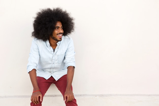 Young man laughing with hands on knees and afro Premium Photo