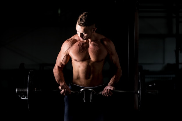 Young man lifting a barbell in gym Free Photo