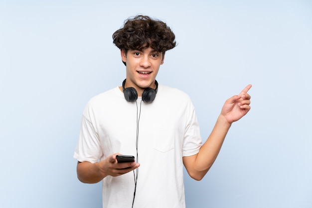 Young man listening music with a mobile over isolated blue wall surprised and pointing finger to the side Premium Photo
