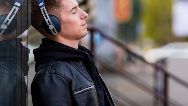 コピースペースとヘッドフォンで音楽を聴く若い男 無料写真
