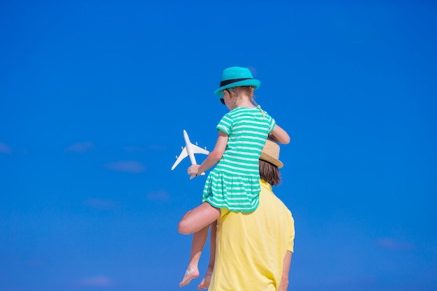 Young man and little girl with miniature of airplane at beach Premium Photo