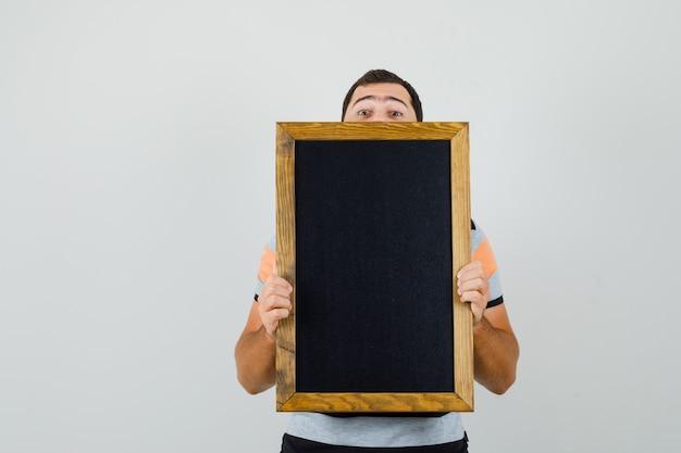 Giovane che osserva sopra la cornice nera in maglietta e cerca spazio nascosto per il testo Foto Gratuite