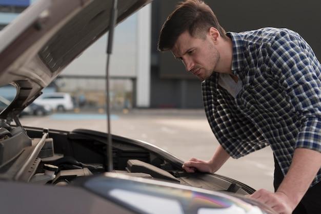Young man looking at car Free Photo