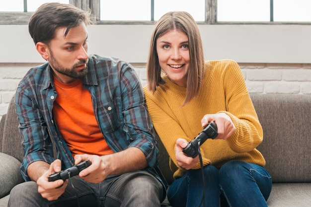 Young man looking at her girlfriend playing the video game with joystick Free Photo