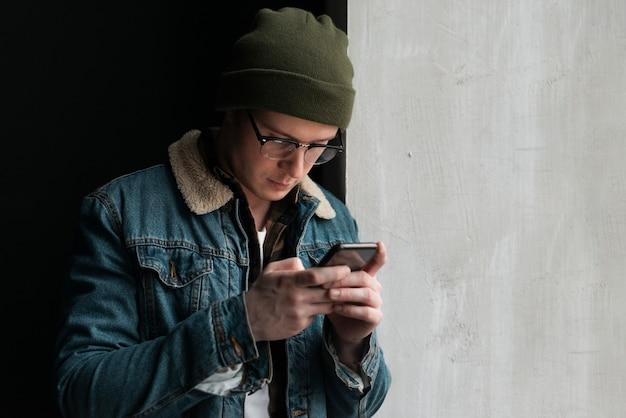 Giovane che esamina il suo telefono con lo spazio della copia Foto Gratuite