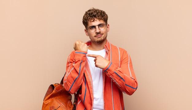 Молодой человек выглядит нетерпеливым и злым, указывая на часы, прося пунктуальности, хочет прийти вовремя. студенческая концепция Premium Фотографии