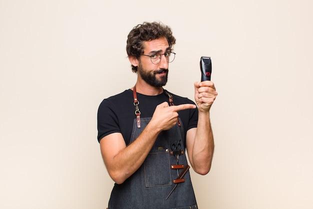Молодой человек выглядит нетерпеливым и сердитым, указывая на часы, прося пунктуальности, хочет прийти вовремя Premium Фотографии