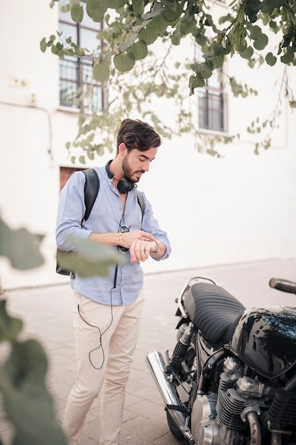 Young man looking at time on watch near his motorbike Free Photo