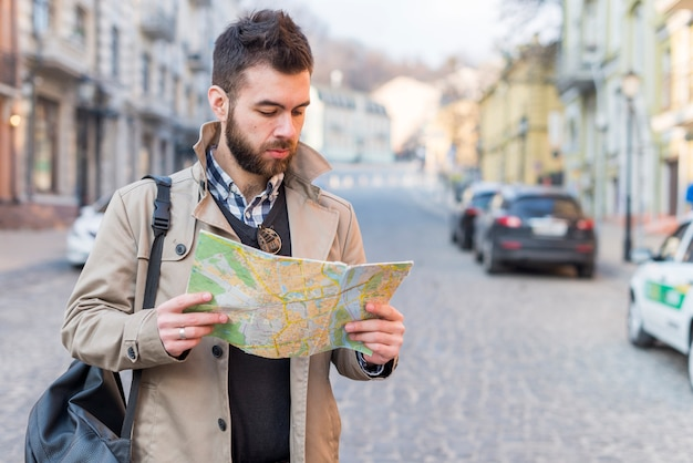 Young man looking for way on destination map; enjoying vacation Free Photo
