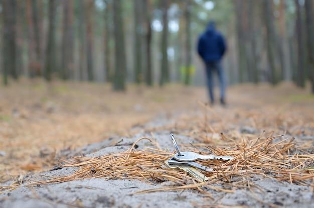 若い男は、ロシアの秋のモミの木の道で彼の鍵束を失います。不注意とキーを失う概念 Premium写真
