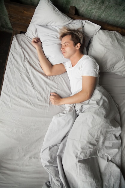 Young man lying asleep sleeping on bed alone, top view Free Photo