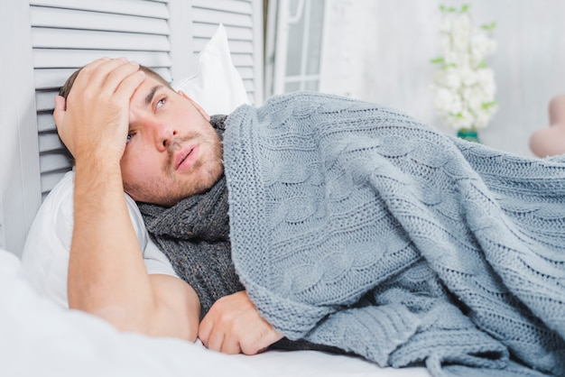 Young man lying on bed with headache and fever touching his forehead Free Photo