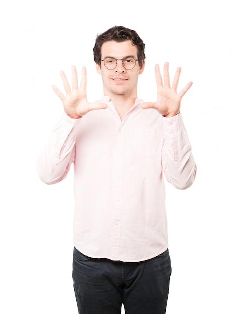 Молодой человек делает жест номер десять Premium Фотографии