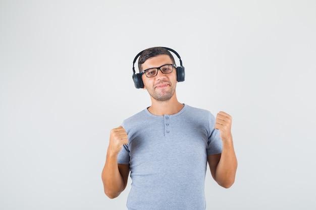 Giovane che fa i pugni alzati in su in maglietta grigia, occhiali, cuffie e che sembra felice Foto Gratuite