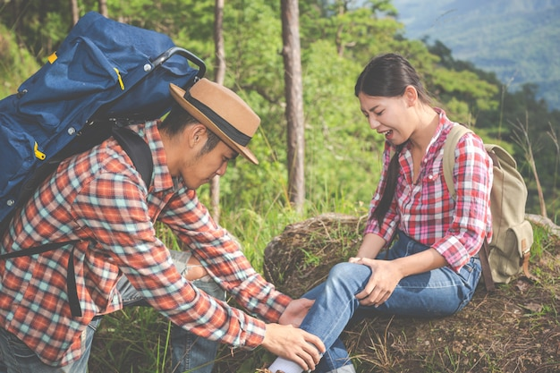 A young man massaging his girlfriend's legs, which pain in the top of the hill in a tropical forest, trekking adventure. Free Photo