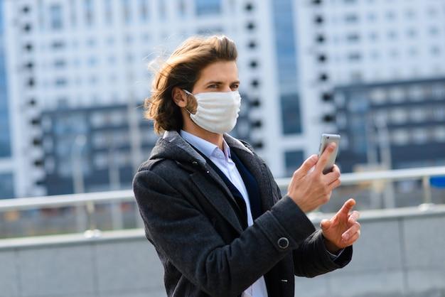 Young man in a medical mask outside, no money, crisis, poverty, hardship. quarantine, coronavirus, isolation. Premium Photo