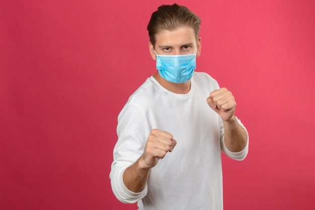 Young man in medical protective mask punching fist to fight standing over isolated pink background Free Photo