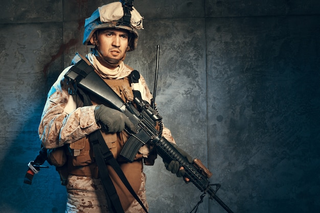 Young man in military outfit a mercenary soldier in modern times on a dark background in studio Premium Photo
